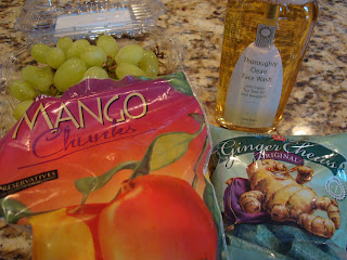 Array of frozen mango chunks, grapes, facial cleanser and ginger chews on countertop