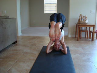 Woman doing half headstand yoga pose