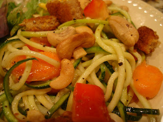 Zucchini noodles with vegetables and peanut sauce on white plate with cashews