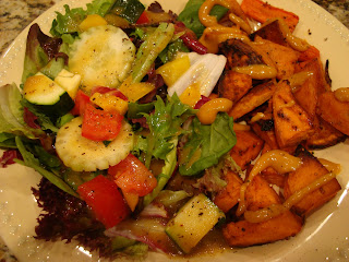 Tossed salad of greens and vegetables on plate with roasted sweet potatoes and carrots