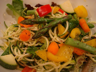 Spiralized zucchini noodles with mixed vegetables topped with dressing