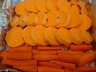 Sliced up sweet potato and carrot sticks in tinfoil lined pan