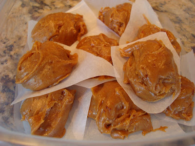 Raw Vegan Peanut Butter Cookie Dough Balls stacked in clear container with parchment paper