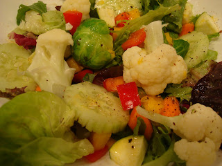 Close up of mixed green and vegetable salad in white bowl