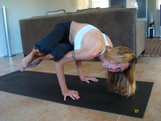 Woman doing Side Crane yoga pose