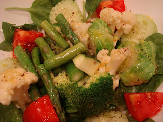 Spinach topped with mixed vegetables in dressing