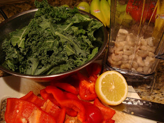 Sliced red pepper, kale, lemon and cashews on countertop