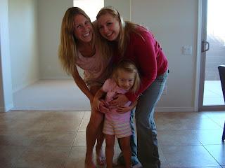 Two woman giving young girl hug