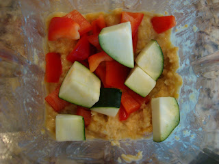Blended hummus ingredients in blender with sliced peppers and zucchini added