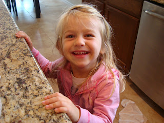 Little girl smiling with hands on countertop