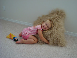 Young girl hugging large brown fuzzy pillow on floor