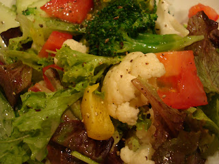 Close up of mixed greens with vegetables and dressing