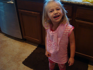Little girl wearing pink smiling standing in kitchen