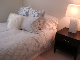 Side view of bed with pillow, black side table and lamp