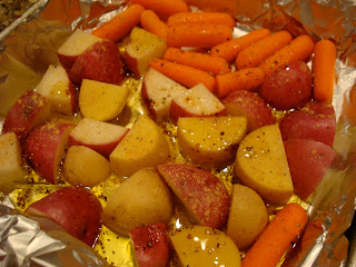 red and yukon gold potatoes, baby carrots with oil, salt, pepper and ginger in foil lined pan