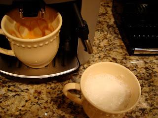 Mug with steamed almond milk and mug in machine brewing espresso