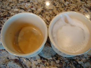 One empty mug and one mug with steamed milk latte