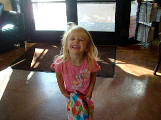 Young girl smiling in front of door holding blanket