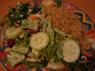 Brown Rice with Garden Salad topped with Slaw Dressing on patterned plate
