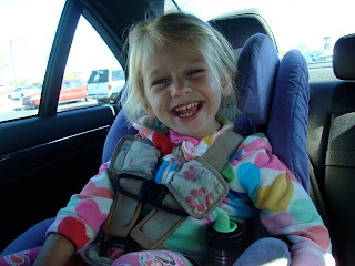Young girl sitting in carseat smiling