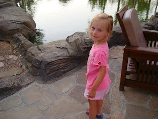 Young girl standing in front of rocks in front of water
