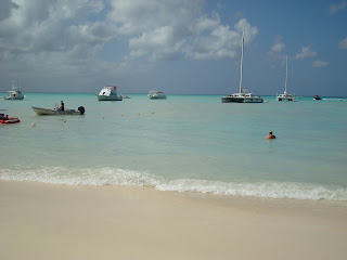 Beach in Aruba showing waves and boats in water