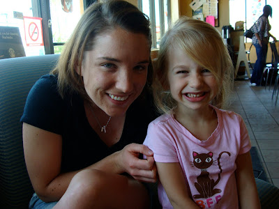 Woman in black shirt next to young girl smiling