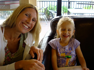Woman crouching next to young girl sitting in chair smiling