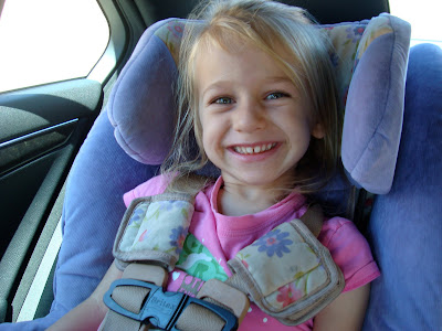Young girl in car seat smiling