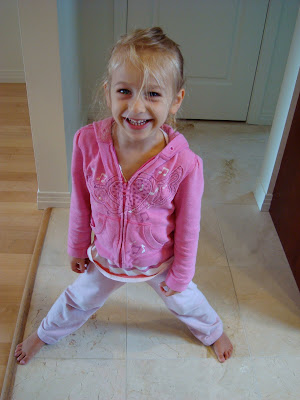 Young girl standing with legs spread smiling by door