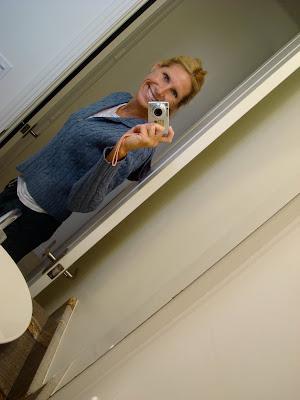 Woman taking photo of self in bathroom mirror