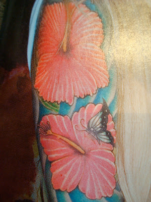 Photo in magazine of arm tattoo of flowers and butterfly