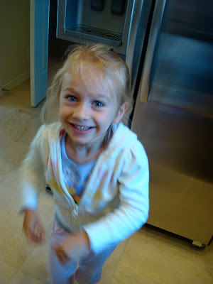 Young girl standing by refrigerator smiling