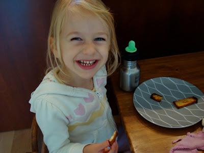 Young girl smiling and eating tofu