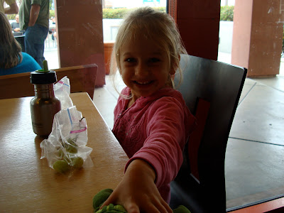 Young girl eating snacks at table and smiling