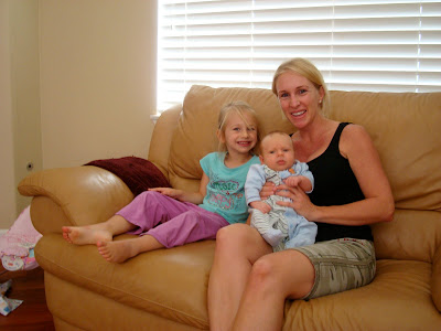 Woman and young girl sitting on couch holding a baby