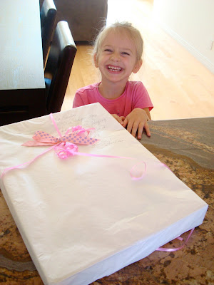 Young girl smiling in front of gift on countertop