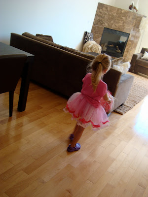 Young girl wearing tutu in dining room