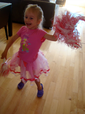 Young girl wearing pink tutu dancing in kitchen