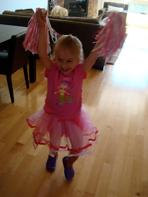 Young girl in tutu holding pompoms