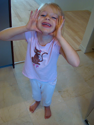 Child with hands on side of face smiling