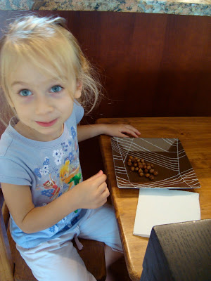Young girl looking at camera eating Carmelized Cinnamon Sugar Roasted Chickpea Peanuts