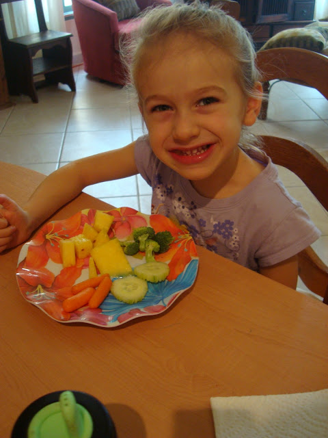 Young girl sitting eating plate of vegetables and fruit