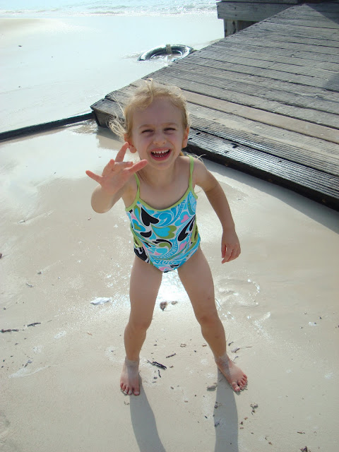 Young girl next to pier with arm up in bathing suit