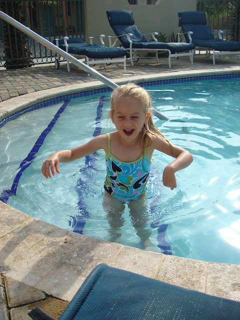 Young girl standing on steps in swimming pool