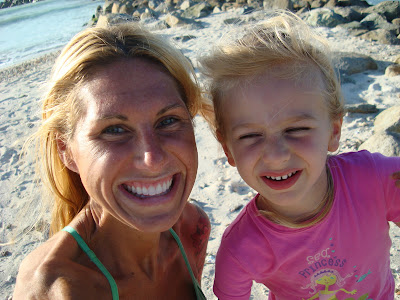 Young girl and woman on beach taking photo together smiling