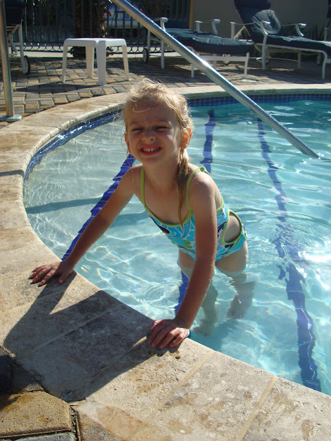 Young girl on pool steps leaning over edge of pool