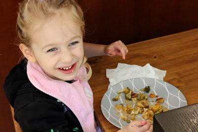 Young girl smiling over almost empty plate