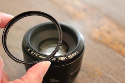 Hand holding UV filter over lens
