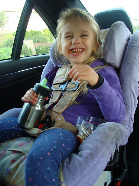 Young girl in carseat eating snacks